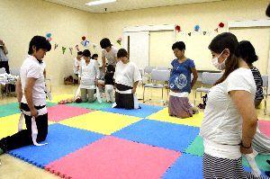 さらしを巻いて骨盤を支える方法を学ぶ妊婦たち=徳島市のときわプラザ