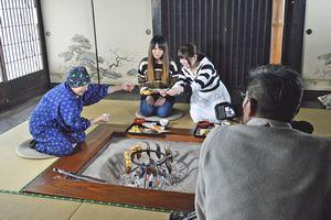 郷土料理を振る舞う都築さん(左端)らを撮影するスタッフ=三好市東祖谷の祖谷八景