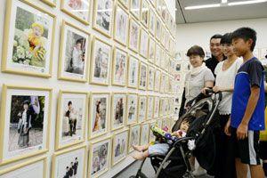 子どもたちの写真に見入る家族連れ=県立近代美術館