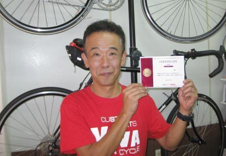 渡し船巡りの「完走」認定証を手にする旅自転車専門店「ナニワ銀輪堂」の中元豊仁さん=大阪市