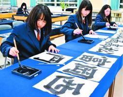 校名の文字を練習する笠井さん(手前)ら=石井町の名西高