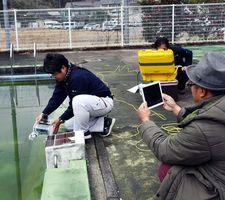 水中ドローン(左)を使って行われた捜索訓練=那賀町和食郷の鷲敷プール