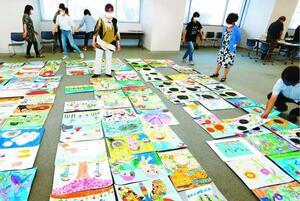 こども県展の絵画作品を見る審査員ら=徳島新聞社