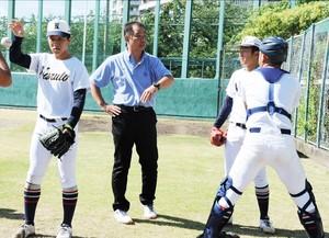 川端さん(中央)からアドバイスを受けるエース西野(右から2人目ら)=兵庫県西宮市の津門中央公園野球場