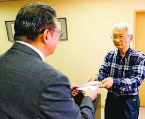 米田代表理事に寄付金を渡す坂東院長(右)=徳島新聞社