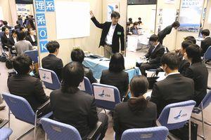 企業のブースで採用担当者の話を聞く参加者=徳島市のアスティとくしま