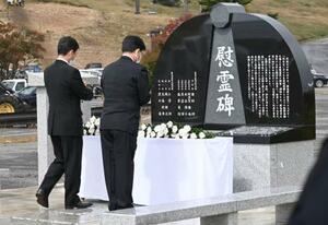 群馬県の防災ヘリコプター墜落事故の追悼式が開かれ、建立された慰霊碑に献花する参列者=25日午前、群馬県中之条町