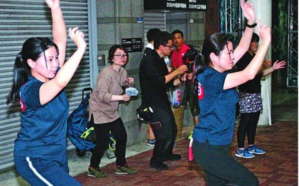 阿呆連の練習を収録する川人さん(左から2人目)ら=徳島市の東新町一丁目商店街