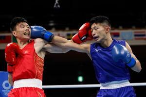 男子フライ級2回戦 2回、中国選手(左)と打ち合う田中亮明=両国国技館