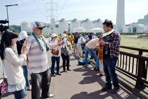 見物人らに「コカちゃんソング」を披露する山下さん(右端)=阿南市橘町の小勝島