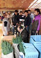 ネギ農家の作業場で話を聞く参加者=石井町高原