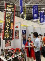 県産食材をバイヤーらに売り込む事業者(左)=東京ビッグサイト(日本政策金融公庫徳島支店提供)
