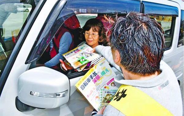 啓発チラシとグッズをドライバーに手渡す参加者=徳島市津田西町2
