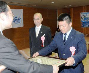 県スポーツ賞のグランプリ賞を受賞し表彰状を受け取る重量挙げの原(右)。中央は指導者の橋本監督=県庁