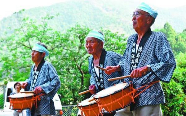 特徴的な動作を繰り返しながら太鼓をたたく保存会のメンバー=美波町赤松