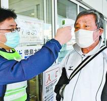 入り口前で検温を受ける利用者=徳島市蔵本町2の徳島大学病院