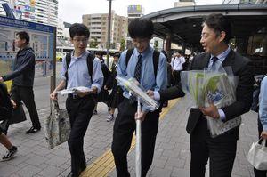 販売店主(右)から朝刊を受け取る通行人=徳島駅前