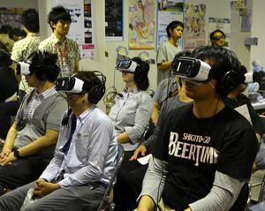 VRの専用ゴーグルとヘッドホンを着け、仮想の世界を楽しむ参加者ら=徳島市の東新町商店街