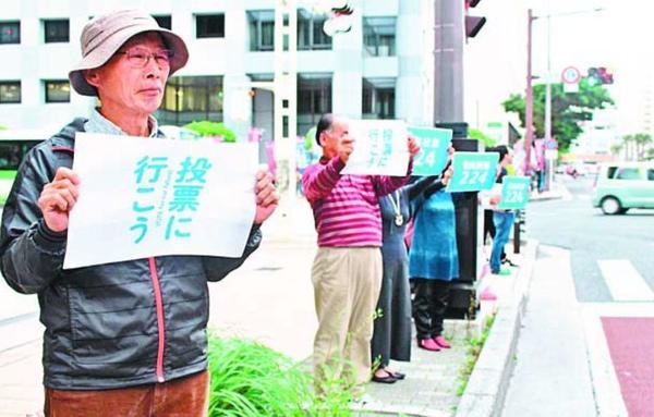 プラカードを掲げ、沖縄県民投票への参加を呼び掛けるOKOKのメンバー=2月16日、那覇市久茂地