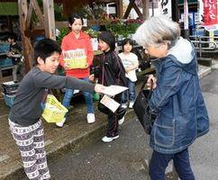 利用者に人権啓発のパンフレットを配る子どもたち=神山町神領の道の駅「温泉の里神山」