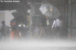 台風5号の強い風雨の中を歩く人たち=7日午前8時25分、JR徳島駅前