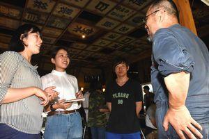 神山の住民(右端)に町の魅力について取材する参加者=神山町神領の寄井座