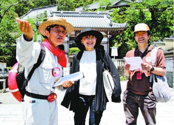 撮影の裏話などを聞きながら映画のロケ地を巡る参加者(中)=美波町奥河内の薬王寺
