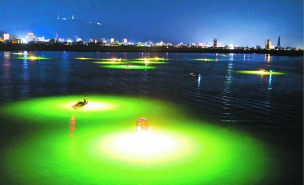 川面で輝く誘魚灯が幻想的なシラスウナギ漁=徳島市の吉野川