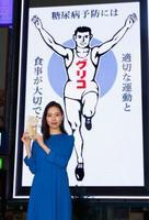 世界糖尿病デーを控え特別演出を実施している江崎グリコの電光看板。手前は女優の戸田恵梨香さん=12日午後、大阪・道頓堀