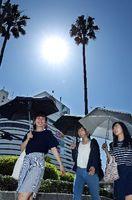 強い日差しが照り付ける中、日傘を差して歩く女性=徳島駅前