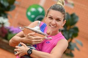 テニスのイタリア国際で優勝し、トロフィーを抱えて笑顔を見せるシモナ・ハレプ=21日、ローマ(AP=共同)