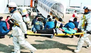 搭乗橋から負傷した乗客を運び出す参加者=松茂町の徳島阿波おどり空港