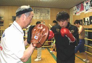 ミットを構え岡田さん(右)に指導する川田会長=阿波市土成町吉田の川田ボクシングジム