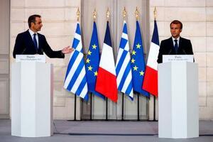 28日、パリで、ギリシャのミツォタキス首相(左)との共同記者会見に出席するフランスのマクロン大統領(AP=共同)