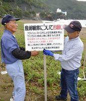 観察時のマナーを記した看板を設置する町ウミガメ保護監視員=美波町の大浜海岸