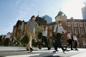 JR東京駅前の交差点を歩くマスク姿の人たち=2日午前