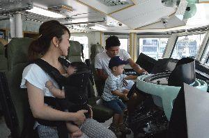 操舵室で座席に座りハンドルを握る親子=小松島市の徳島小松島港新港