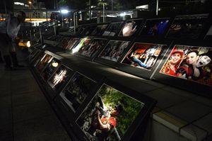 夜に懐中電灯で照らして見る写真展のリハーサルをする塾生=徳島市のあわぎんホール