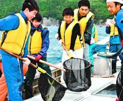 取った魚を漁船の水槽に移す生徒たち=美波町の伊座利漁港沖