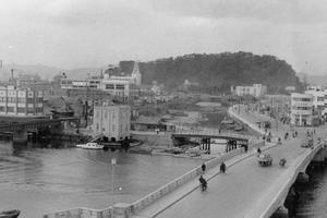 今から60年前の徳島市中洲町1付近。このころには寺島川の一部が残り、その横を国道11号が通っていた=1961(昭和36)年、津田明彦さん提供