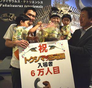 来場者6万人目の記念品を吉村局長(右)から受け取る山下晃希ちゃん(左手前)=県立博物館