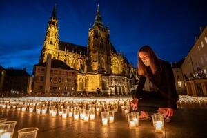10日、チェコ・プラハ城で、ろうそくに火を付ける女性(ゲッティ=共同)