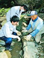 明石さん(右端)に教わりながら石を積む新入社員=吉野川市美郷平
