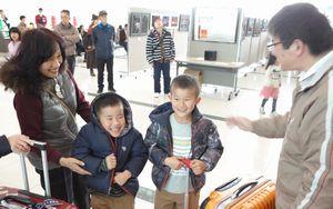 祖父母の出迎えを受け、笑顔を見せる子ども=徳島空港