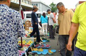 品定めする徳島びっくり日曜市の買い物客。15日に開設20周年を迎える=2016年6月12日、徳島市問屋町(日曜市事務局提供)