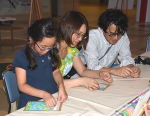 マスキングテープで絵を制作する親子連れ=鳴門市鳴門町の大塚国際美術館