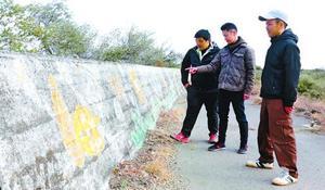 約30年前に描かれた壁画再生に取り組む春野部長(右)ら=阿南市那賀川町の出島海岸