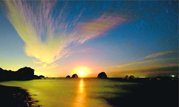 空と海をオレンジ色に染めながら上る月。幻想的な光景だった=阿南市中林町