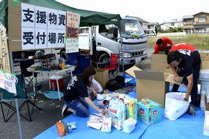集められた物資を仕分けるMOVEのメンバー=徳島市の平惣川内店前の駐車場