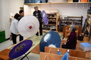 観光客(左の2人)に和傘の説明をするメンバー=美馬市脇町の市伝統工芸体験館